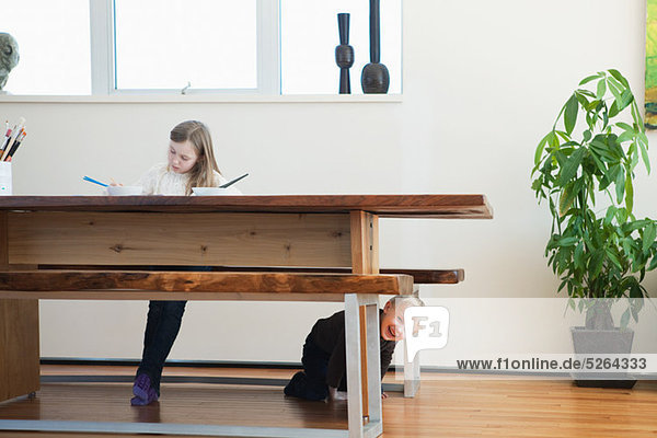 Girl painting  brother under table