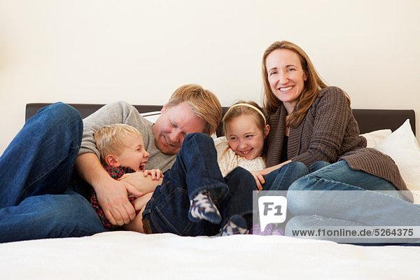 Familie auf dem Bett sitzend  Portrait