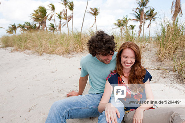Young couple sitting on beach  portrait