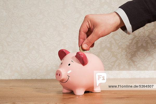 Mann  der Pfundmünze ins Sparschwein steckt