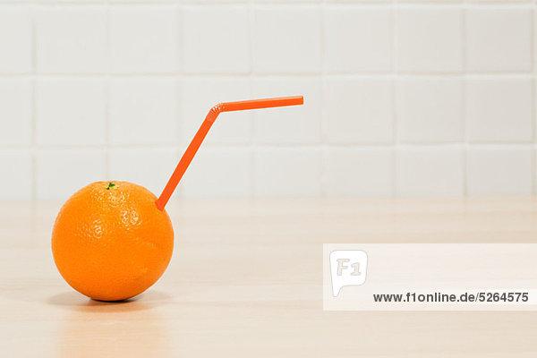 Orange mit herausstehendem Trinkhalm