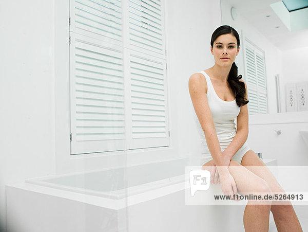 Junge Frau sitzend am Rand der Badewanne