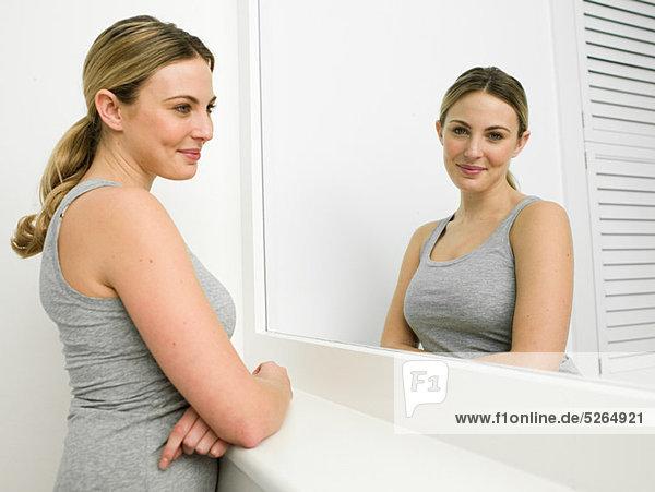 Reflexion der junge Frau im Badezimmerspiegel