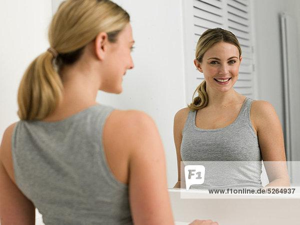 Reflektion der jungen Frau im Badezimmerspiegel