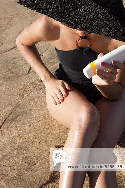 Junge Frau beim Auftragen von Sonnencreme am Strand