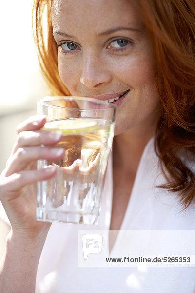 Mädchen mit rotem Haar zu gießen und Trinkwasser