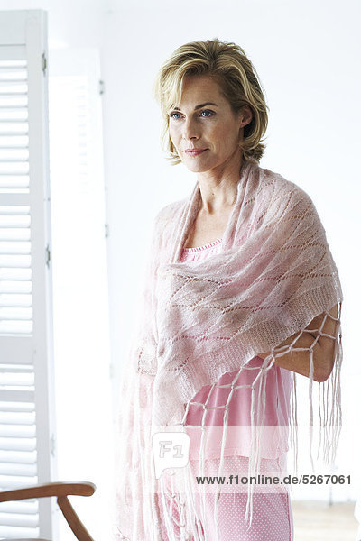 Mature  relaxed woman in pink pyjamas and wrap