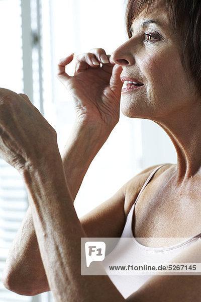 Reife Frau entfernen Augen Make-up mit Wattestäbchen