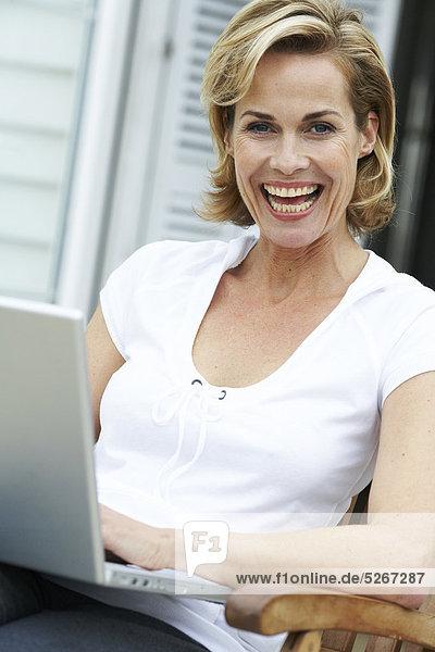 Reife Frau auf ihre Arbeiten fort ihr Laptop beachouse