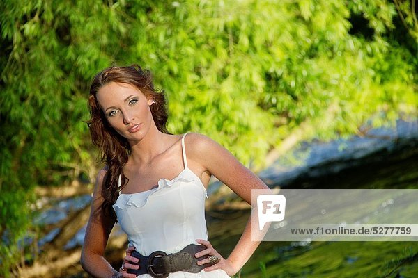 A beautiful young caucasian woman outdoors in Spokane  Washington  USA  standing in the Spokane River.