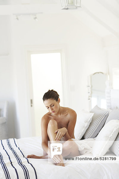 Schöne nackte Frau sitzen feuchtigkeitsspendende Beine