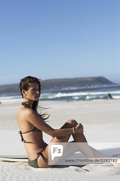 Mädchen am Strand mit Surfbrett sitzen