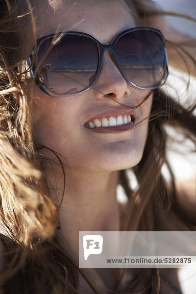 Girl on Beach with windswept Hair mit Sonnenbrille