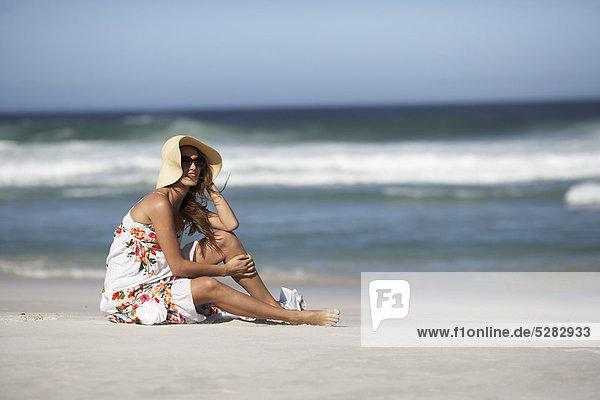 Mädchen in Hut auf windigen Strand