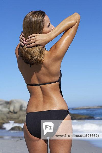 Rückseite Schuß Frau spielen mit Haaren am Strand