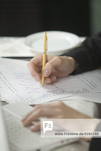 detail of businesswoman writing document during business lunch