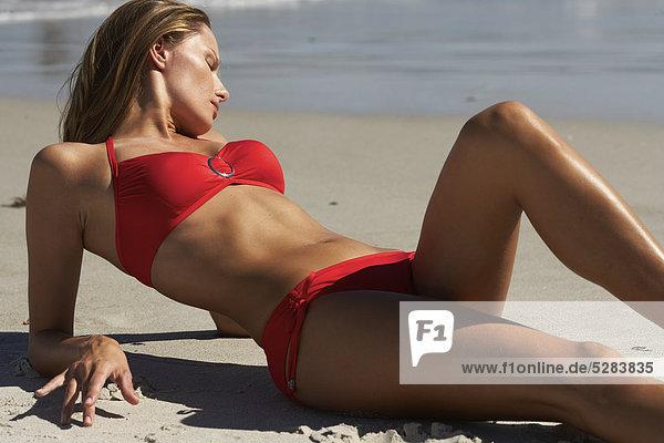 Frau im roten Bikini am Strand sonnen