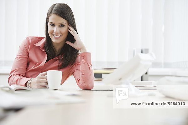 Portrait of young Businesswoman sitting at Desk mit cup