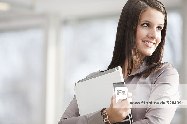 portrait of young businesswoman with documents and mobile phone