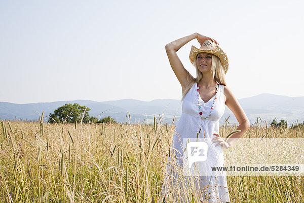 Junge Frau mit Hut stehen im Feld