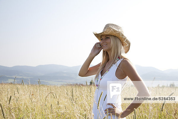 Portrait of young Woman standing in Feld talking on Mobile phone