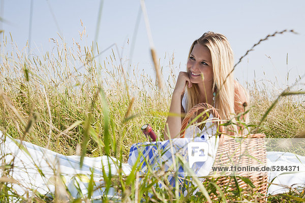 Portrait of young Woman sitting in Wiese mit Picknick