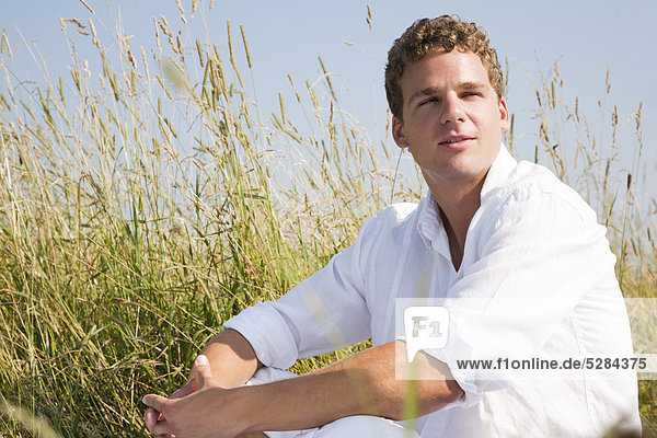 portrait of young man sitting in meadow