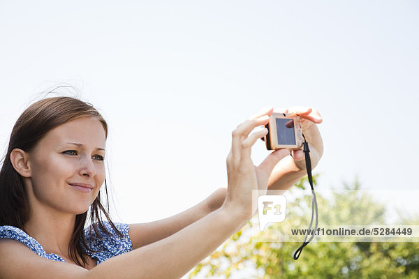 young woman taking picture of herself with digital camera
