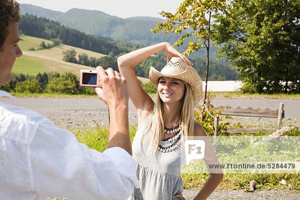 junge Mann nehmen Portrait Freundin mit Digitalkamera
