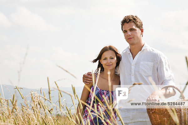 Portrait of young Couple mit Picknick-Korb im Feld