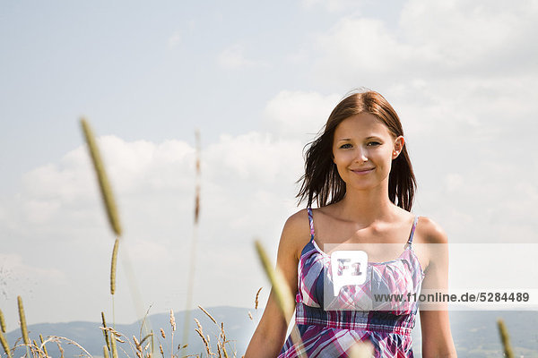 Portrait of young Woman standing in Feld