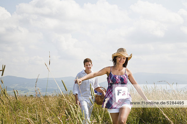 junges Paar mit Picknick-Korb  die durch Feld