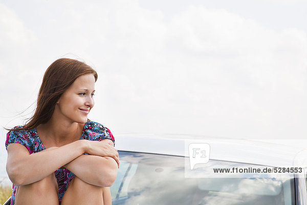 Portrait of young Woman sitting on Motorhaube  Auto