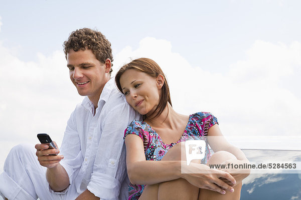 portrait of young couple man writing text message on mobile phone