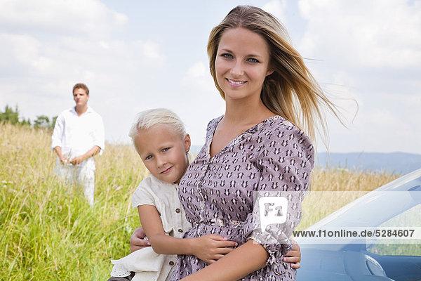 Porträt der jungen Frau und Tochter auf Auto