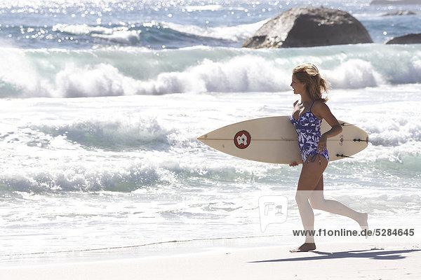 Landschaft frisch konfrontiert Frau am Strand mit surfboard