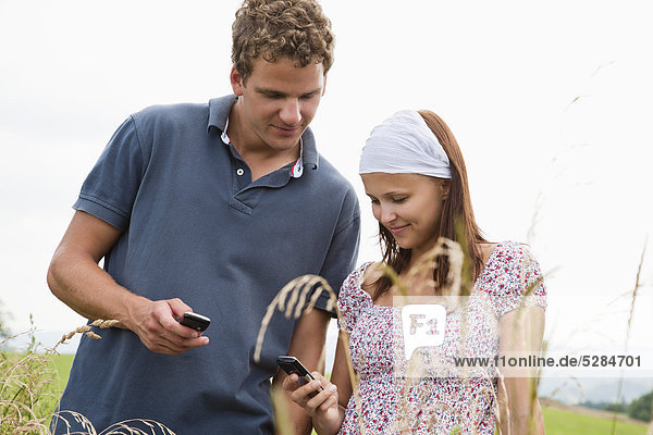 portrait of young couple checking their mobile phones for text messages