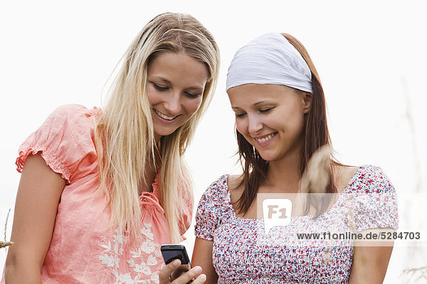 two young woman reading text message on mobile phone
