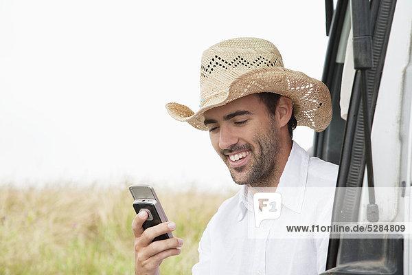 Portrait of young Man Stroh Hut mit Mobiltelefon