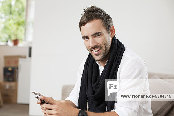 portrait of young man with mobile phone sitting at home