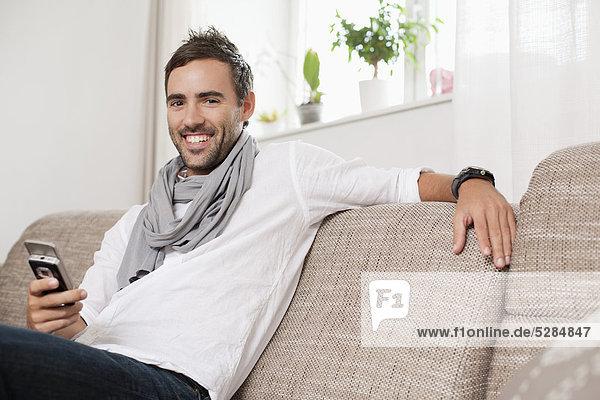 Handy  sitzend  Interior  zu Hause  Portrait  Mann  Kurznachricht  jung