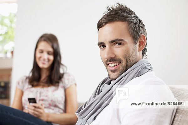 portrait of young man at home with girlfriend in background
