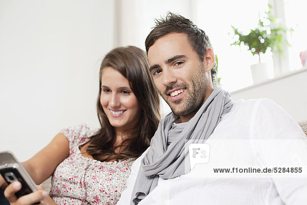 Portrait of young Couple sharing Textnachricht auf Handy