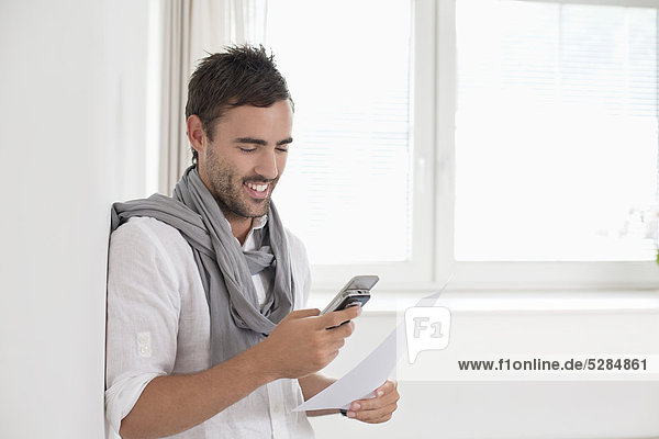 portrait of young man in empty room with mobile phone