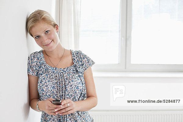 Portrait of young Woman in leeren Raum mit Mobiltelefon