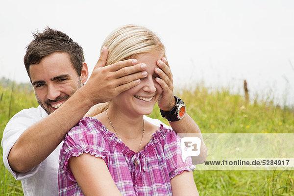 junger Mann spielen Peekaboo mit Freundin