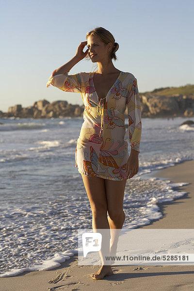 Reife Frau zu Fuß am Strand  am späten Nachmittag