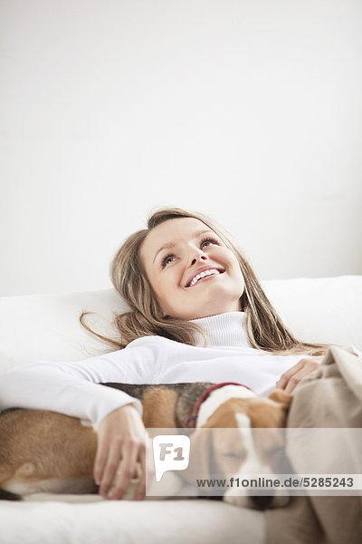 Portrait of young Woman zusammen auf Sofa mit Hund