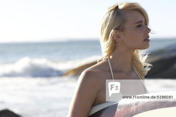 Blonde Mädchen am Strand mit surfboard