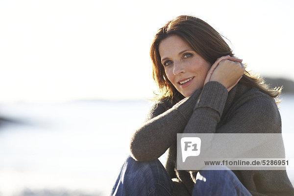 Landschaft der schöne Reife Dame am Strand sitzen